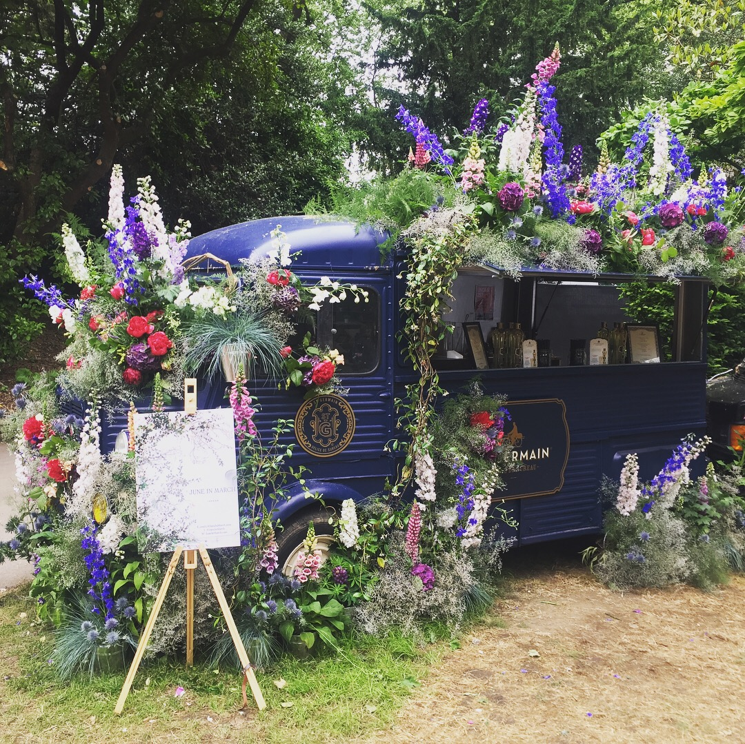 A van-come-bar covered in flowers.
