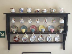 Quaint tea cups line the wall.